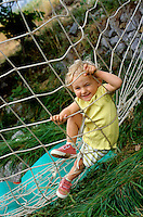 Two year old girl playing on a climbing net.