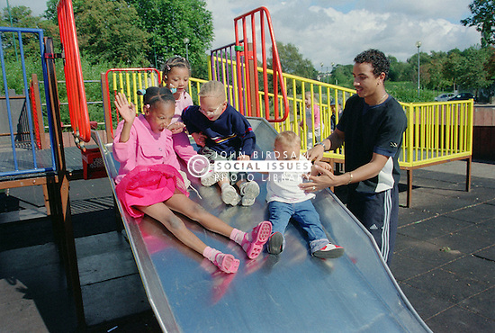 Father supervising multiracial group of children playing on slide in playground,
