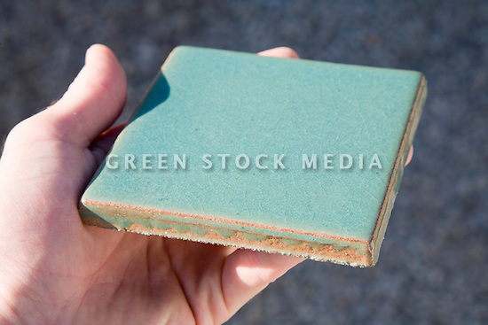 A hand holding a glazed tile with 40% recycled ceramic content. model released