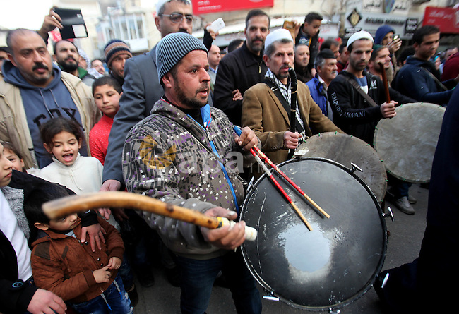 """Palestinians Muslim Sufis play musical instruments as they parade through the streets during a ceremony commemorating the birth of Prophet Mohammed, known in Arabic as """"Mawlid al-Nabawi"""", in the West Bank city of Nablus on December 11, 2016. Photo by Nedal Eshtayah"""