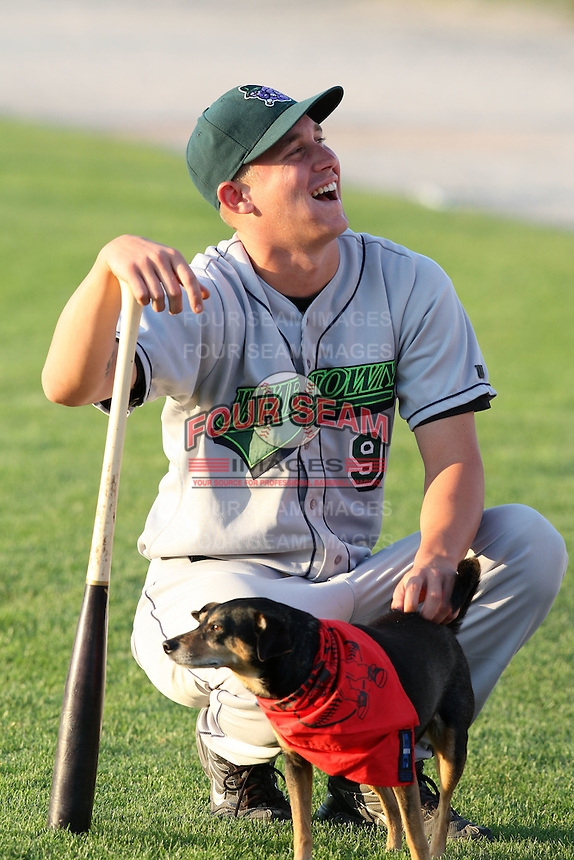 "September 5, 2009:  Chad Cregar of the Jamestown Jammers pets ""Haley"" (Batavia Groundskeeper Don Rock's dog) before a game at Dwyer Stadium in Batavia, NY.  The Jammers are the NY-Penn League Short-Season Class-A affiliate of the Florida Marlins.  Photo By Mike Janes/Four Seam Images"