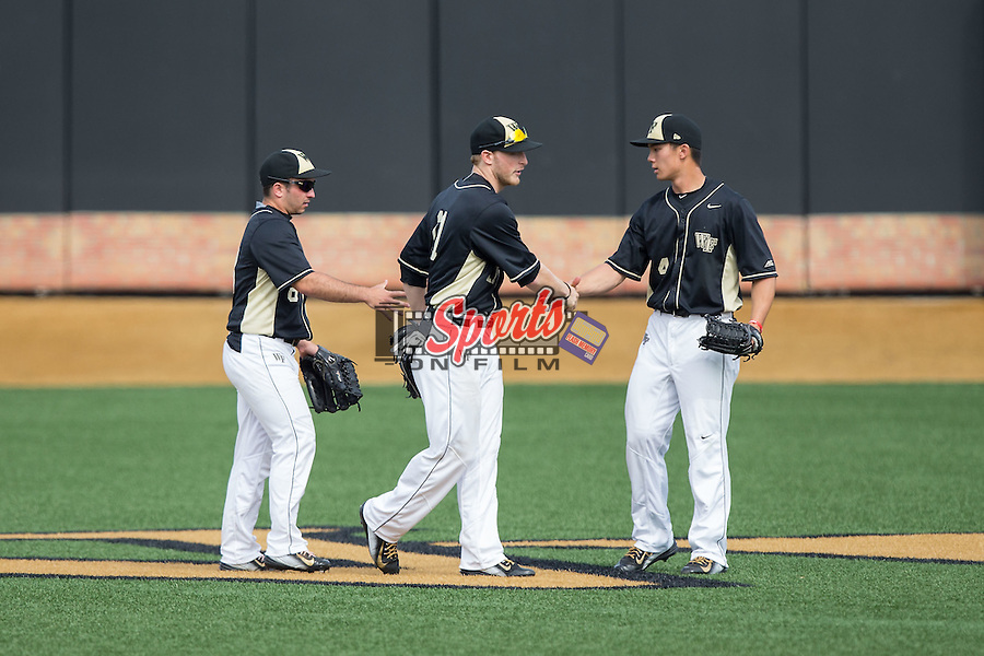 (L-R) Wake Forest Demon Deacons outfielders Joey Rodriguez (8), Jonathan Pryor (11), and Stuart Fairchild (4) shake hands after their win over the Miami Hurricanes at Wake Forest Baseball Park on March 22, 2015 in Winston-Salem, North Carolina.  The Demon Deacons defeated the Hurricanes 10-4.  (Brian Westerholt/Sports On Film)
