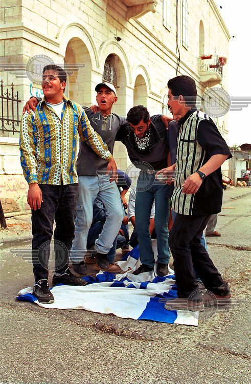 Palestinian men provoke Israeli soldiers by trampling on the Israeli flag, during clashes in the West Bank city of Bethlehem..The clashes took place against a background of growing Palestinian frustration with the  peace negotiations with Israel..