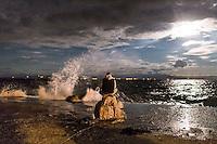 GRIECHENLAND, 09.2015, Insel /Island of/ Lesbos. Internationale Fluechtlingskrise: Jeden Tag kommen ca. 50 ueberfuellte Boote aus der nahen Tuerkei an. Hier beginnt fuer die Fluechtlinge und Migranten ihr Weg durch Europa. -Die Menschen warten darauf, mit grossen Faehrschiffen vom Hafen Mytilini aufs griechische Festland gebracht zu werden. Hinten die tuerkische Kueste bei Mondlicht. | International refugee crisis: Everyday around 50 overcrowded boats arrive from nearby Turkey. Here the refugees' and migrants' journey through Europa begins. -People waiting for the big ferries to take them from the port of Mytilini to the Greek mainland. In the background the Turkish coast in moon light.<br /> © Arturas Morozovas/EST&OST