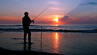 Rick Wilson Photo--6/8/04--A surf fisherman casts for whiting in the calm surf of the Atlantic Ocean from Jacksonville Beach, Florida at sunrise.