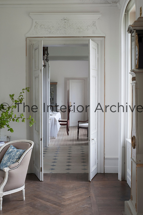 Double doors from the living room are graced with a carved plaster pediment and open onto the entrance hall and the dining room beyond