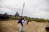 Teenagers play while watching the competition at the Mechanical Bull-A-Rama at the Whoa Arena in Valier, Montana, USA.  The event, organized by Janelle Nelson, was a benefit for local youth rodeo participants and the local food bank.