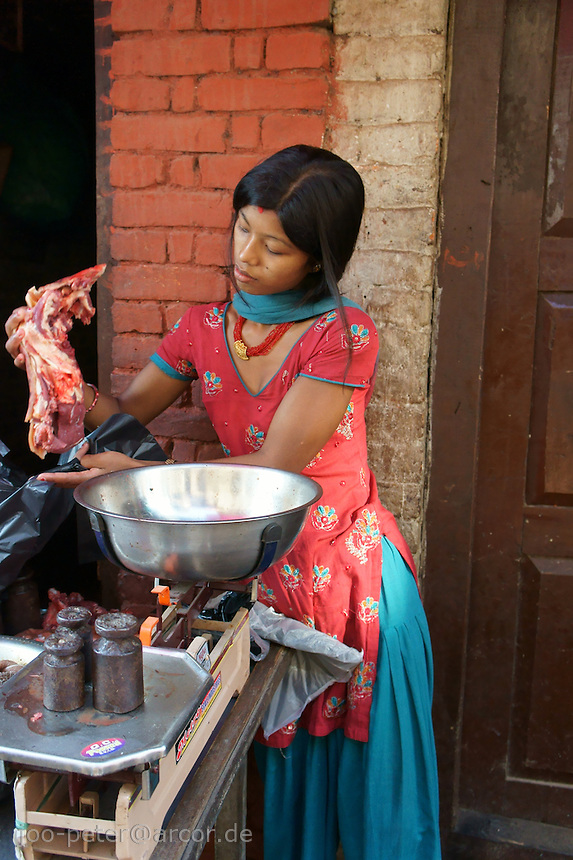 woman selling meat of a sacfrificed buffalo during dashein festival time in Bhaktapur, Nepal. October 2011