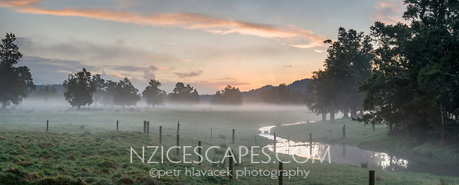Moody scene of farmland in Whataroa with creek at sunset,  West Coast, South Westland, New Zealand, NZ