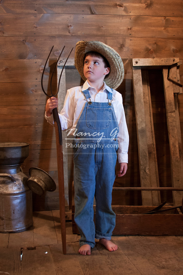 A young farmer boy holding a pitch fork