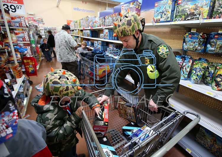 Wearing matching bike helmets, Carson City Sheriff's Deputy Craig Erven helps two of nearly 170 elementary students shop as part of the Holiday with a Hero program at Walmart in Carson City, Nev., on Tuesday, Dec. 17, 2013. The community event partners military, firefighters, law enforcement and medical personnel with local Students in Transition to provide them with Christmas presents.<br /> Photo by Cathleen Allison