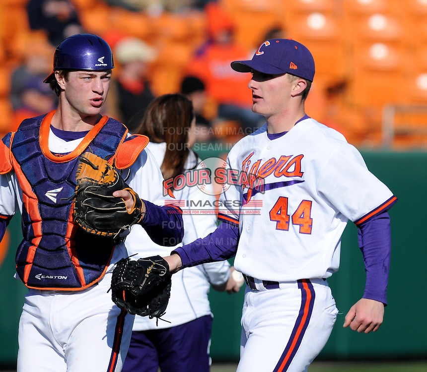 Starting pitcher Matthew Crownover (44) of the Clemson Tigers is congratulated by catcher Garrett Boulware (30) after the first inning of a game against the Wofford Terriers on Wednesday, March 6, 2013, at Doug Kingsmore Stadium in Clemson, South Carolina. Clemson won, 9-2, with freshman Crownover picking up his first win.  (Tom Priddy/Four Seam Images)
