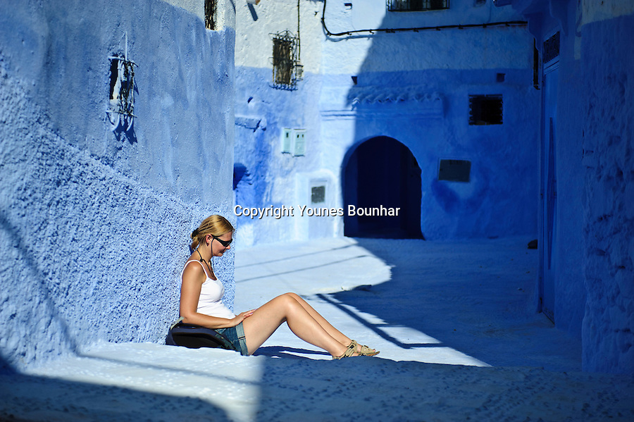 A European tourist enjoys the sun in the mesmerizing blue streets of Chefchaouen (at the foot of the Rif mountains of Morocco)
