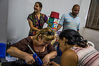 "RIO DE JANEIRO, BRAZIL - FEBRUARY 21, 2014: (Right) Samy das Chagas, a visual artist and mental health patient, puts finishing touches onto a manequin made of prescription medecine that is used to treat schizophrenia and bipolar disorder, with the help of another patient and a (Top Left)Polyanna Ferrari, a co-ordinator, in preparation for the annual Tá Pirando, Pirado, Pirou! carnival street parade at the Instituto Philippe Pinel psychiatric hospital on February 21, 2014 in Rio De Janeiro, Brazil. It looks like any of the other 450 or so street parties, locally called ""carnival blocks,"" that parade through Rio de Janeiro during the raucous pre-Lenten festivities that draw hundreds of thousands to the city each year. What makes this party different are its performers and organizers: psychiatric patients and their doctors, therapists, family members, neighbors and passers-by. The group, called Tá Pirando, Pirado, Pirou!, which roughly translates as ""We're freaking out, we already freaked out!"", began ten years ago when Brazil was in the process of dismantling its century-old system of mental asylums. A law passed in 2001 called for long-term outpatient psychiatric care to be offered primarily in community clinics. The number of such clinics increased more than fivefold in the following decade, while the number of asylum beds for psychiatric patients dropped 40 percent nationwide.<br /> <br /> Daniel Berehulak for The New York Times"