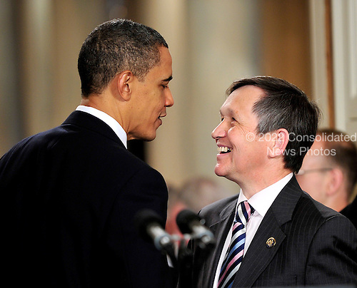 Washington, D.C. - March 23, 2010 -- United States President Barack Obama, left and U.S. Representative Dennis Kucinich (Democrat of Ohio) exchange some thoughts after the President signed the version of the health care bill that was passed by the U.S. House of Representatives in the East Room of the White House in Washington, D.C. on Tuesday, March 23, 2010..Credit: Ron Sachs / CNP.(RESTRICTION: NO New York or New Jersey Newspapers or newspapers within a 75 mile radius of New York City)