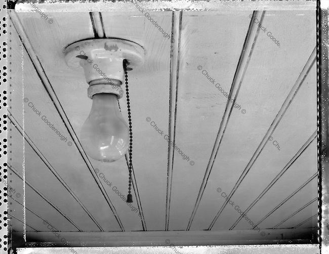 Black & White Photo of a single light bulb fixture on the ceiling of an old kitchen, pantry or porch.