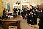 United States President Donald Trump signs his first executive order as president, ordering federal agencies to ease the burden of President Barack Obama's Affordable Care Act, in the Oval Office at the White House in Washington, D.C. on January 20, 2017. <br /> Credit: Kevin Dietsch / Pool via CNP