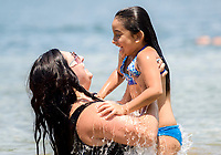 NWA Democrat-Gazette/CHARLIE KAIJO (From left) Mel Reyes of Rogers holds up her daughter Jazlynn Cortez, 6, during a warm afternoon, Sunday, July 8, 2018 at the Prairie Creek Marina in Rogers.