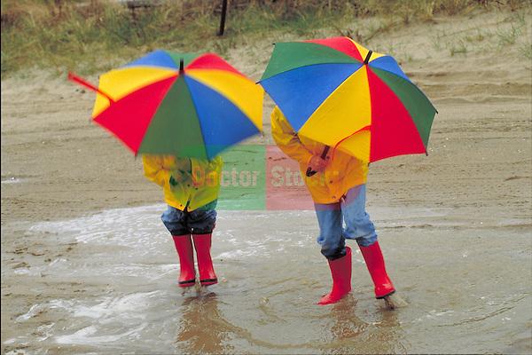 children holding umbrellas at the beach in the rain