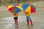 children holding umbrellas at the beach in the rain