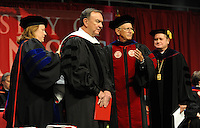NWA Media/ANDY SHUPE - Mike Duke, former president and CEO of Walmart Stores, Inc., center, waits as Sharon Gaber, provost and vice chancellor for academic affairs at the University of Arkansas, left; Jim von Gremp, chairman of the university's Board of Trustees; and David Gearhart, chancellor of the university, right, bestow upon him an honorary degree during fall commencement exercises Saturday, Dec. 20, 2014, at Barnhill Arena on the university campus in Fayetteville.