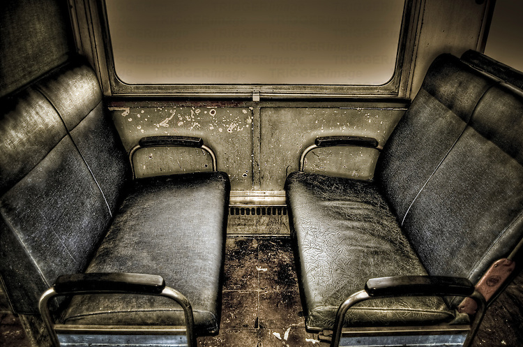 Interior of old train carriage with black seats