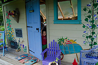 Little girl peeks out door of painted shed in community Garden, Maine USA