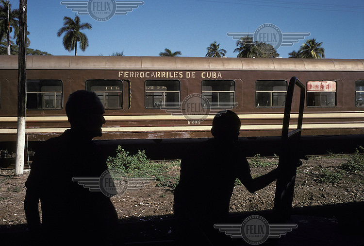 Railway workers silhouetted against a carriage at Cienfuegos Station.
