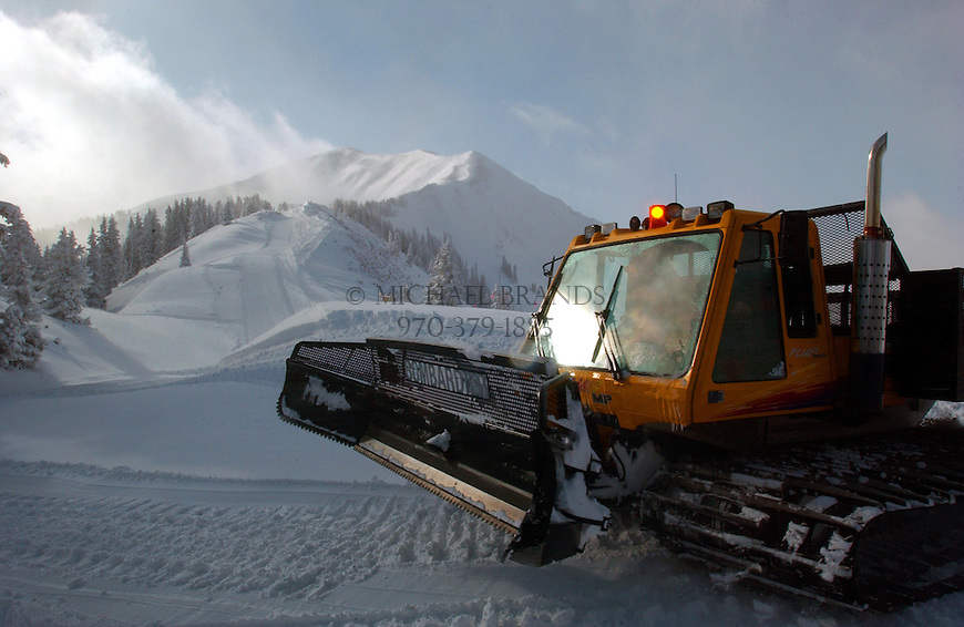 A snowcat waits to pick up skiers at the base of Highland Bowl, background. The snowcat delivers a short ride. The summit is reached by hiking. © Michael Brands. 970-379-1885. ski, skiing,