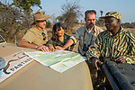 African Lion (Panthera leo) biologists, Jake Overton, Kim Young-Overton, and Luke Hunter, discussing poaching activities with park scout, Timbo Frackson, Kafue National Park, Zambia