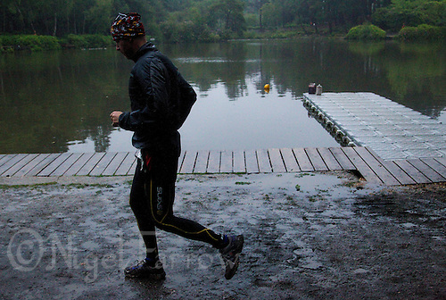 12 JUN 2011 - BRANSGORE, GBR - As dusk falls on day 10, Tony Raynor runs past the swim lake as he completes the last few miles of the Deca Enduroman at the Enduroman Ultra Triathlon Championships (PHOTO (C) NIGEL FARROW)