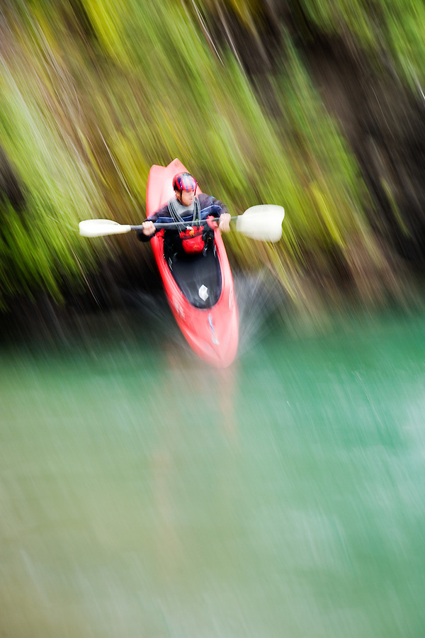 Male whitewater kayaker seal launches into the Kananaskis River just upstream from Widow Maker rapid, Kananaskis County, Alberta, Canada