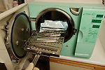 A gloved hand inserts used dental tools into an autoclave to be sterilized by high pressure steam. Royalty Free