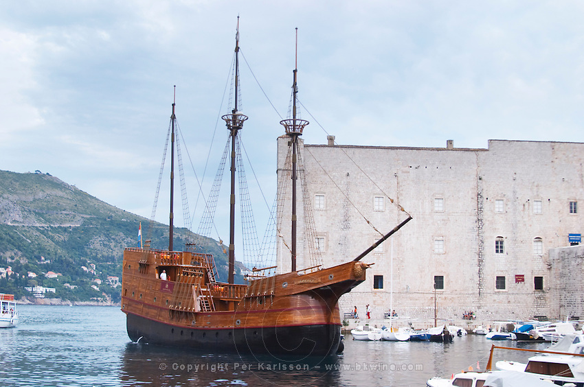 The Karaka 16 century galleon replica boat in the old harbour. The Saint John's fort in the background Dubrovnik, old city. Dalmatian Coast, Croatia, Europe.