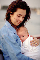 Mother, Christine, cuddling with newborn baby Alexander, infant, motherhood, love, security, babies and their mothers. Alexander and Mom. Santa Monica California.