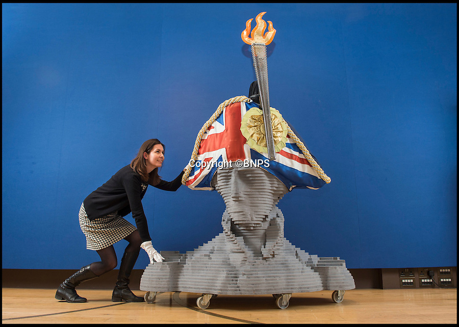 BNPS.co.uk (01202 558833)<br /> Pic: PhilYeomans/BNPS<br /> <br /> England expects...Expert Anna Evans carefully wheel's in the huge hat.<br /> <br /> If you want to get ahead get a hat - £12,000 could secure you a unique piece of British sporting and military history with the sale of the Sylvia Fletcher designed hat that sat on the top of Nelson's column during the 2012 Olympics in London. <br /> <br /> The unusual item is part of the 'Style and spirit' sale at Christies this week and includes an original Olympic torch and wooden bust of the great naval hero.<br /> <br /> Unfortunately, being 6ft high and nearly 4ft wide, it won't be possible to wear the unique design, but it could be the ultimate 'statement piece' for a modern home.
