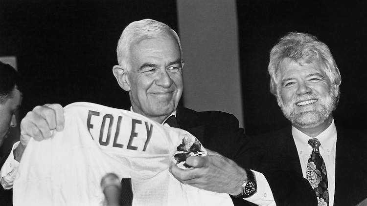 "Speaker of the House Rep. Thomas Stephen ""Tom"" Foley, D-Wash holding up a Washington Huskies Jersey given him by the Washington Huskies Football Team. The Education Association Member of Washington Delegation received a jersey and a football signed by the players. Representative Jim McDermott at right. March 14, 1992 (Photo by Maureen Keating/CQ Roll Call)"