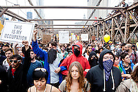 "Protesters march across the Brooklyn Bridge as ""Occupy Wall Street"" hits its two week anniversary in New York City on October 1, 2011."