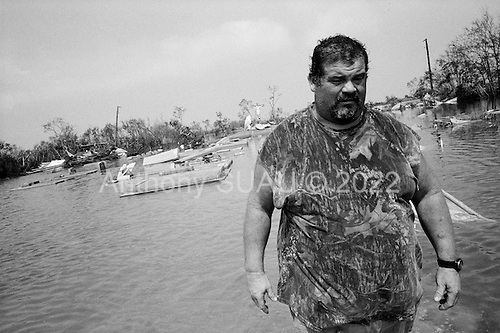 Cameron, Louisianna.USA.September 27, 2005 ..Hurricane Rita damage and recovery in the town of Cameron...Three residents return by small boat illegally to the town. Lawrence Landry 42, (shorts no shirt), Henry Roy Jr.49 (big guy) in shorts and older man, Roddy Aguillard, 59, as they visit their homes and town. All are shrimpers. ..Henry and Lawrence look for relatives in the town's cemetery. Coffin's float on the water.