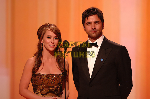 "JENNIFER LOVE HEWITT & JOHN STAMOS.Present the award for Best Performance by an Actress in a Television Series - Musical or Comedy for ""Ugly Betty"".Telecast - 64th Annual Golden Globe Awards, Beverly Hills HIlton, Beverly Hills, California, USA..January 15th 2007. .globes half length microphone stage black tuxedo jacket bronze gold dress.CAP/AW.Please use accompanying story.Supplied by Capital Pictures.© HFPA"" and ""64th Golden Globe Awards"""