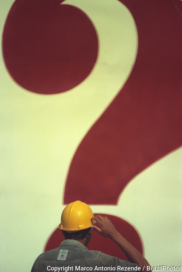 Construction worker in front of a question mark.