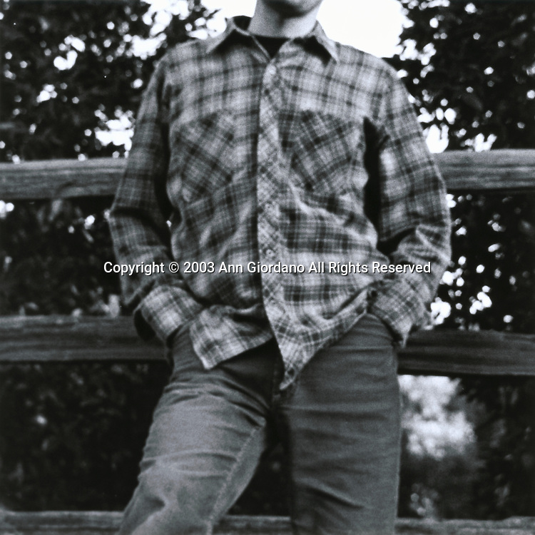 View of man from chin to knee in flannel shirt and jeans leaning up against wooden rail fence