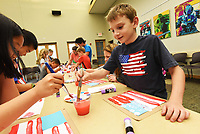 """NWA Democrat-Gazette/FLIP PUTTHOFF <br /> SALUTE TO THE FLAG<br /> Isaac Shackelford (cq), 8, sports a patriotic shirt Wednesday July 3 2019 while painting an American Flag at the Bentonville Public Library. Isaac's cousin, Heyley Shrum (second from right), 11, paints a flag. The art project was part of the """"Salute to the Flag"""" activity for children. Kids learned about the first lunar landing and painted a flag similar to the flag astronauts unfurled on the moon. They heard the story """"One Giant Leap"""" in observance of the 50th anniversary of the first lunar landing that took place on July 20, 1969."""
