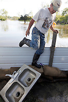 Bill Sandquist returns from a canoe trip down North Main Street with a complete Delta faucet system. Debris is starting to pile up in the Mississippi River floodwater that has engulfed the Red Star District of Cape Girardeau, MO.