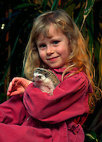 Young girl holding her unusual pet - an African Pygmy Hedgehog.