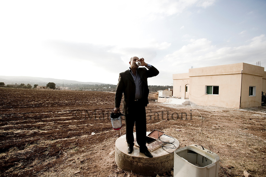 JORDAN - AS SALT -  Eng.Sameeh Al Nuimat, PROJECT MANAGER FOR CARE, TASTING THE WATER OF THE WATER RESERVOIR WHICH BELONGS TO THE CARE PERMACULTURE PROJECT