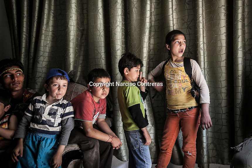 "Kurdish youth and children, who support the ""Popular Protection Units"" (YPG), stand inside a house as they refuse to leave their home in the majority-Kurdish Sheikh Maksoud district after Syrian opposition fighters entered into the neighborhood forcing thousands of civilians to flee into safe areas outside of Aleppo City. Since then, the neighborhood is being bombed and shelled by Syrian forces in its attempt to sweep out the opposition fighters from the area."