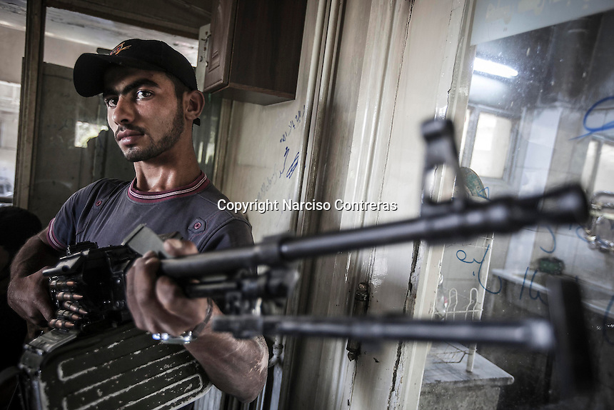 A rebel fighter belonging to the Liwa Al Tawhid posses for a picture as he takes a rest at the rebel post in Zahoor before move to the fighting at the Saif Al Dawla battlefield in southwest of Aleppo City. During last days the first line of fighting have moved into Saif Al Dawla residential neighborhood for the control of the area.