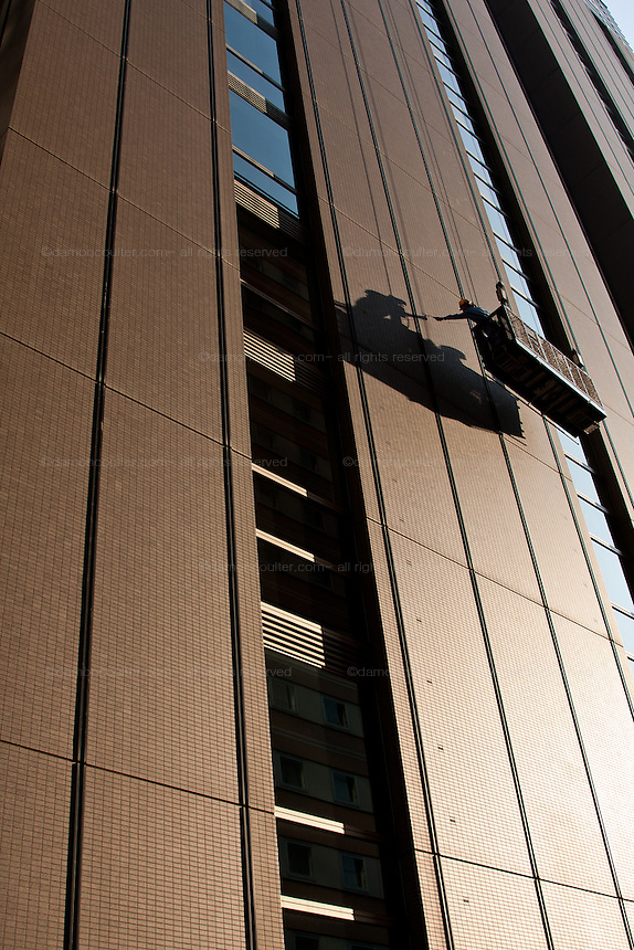 Window cleaners and building maintenance engineers  on the side of Mynds Tower in a Shinjuku, Tokyo, Japan Wednesday September 22nd 2010