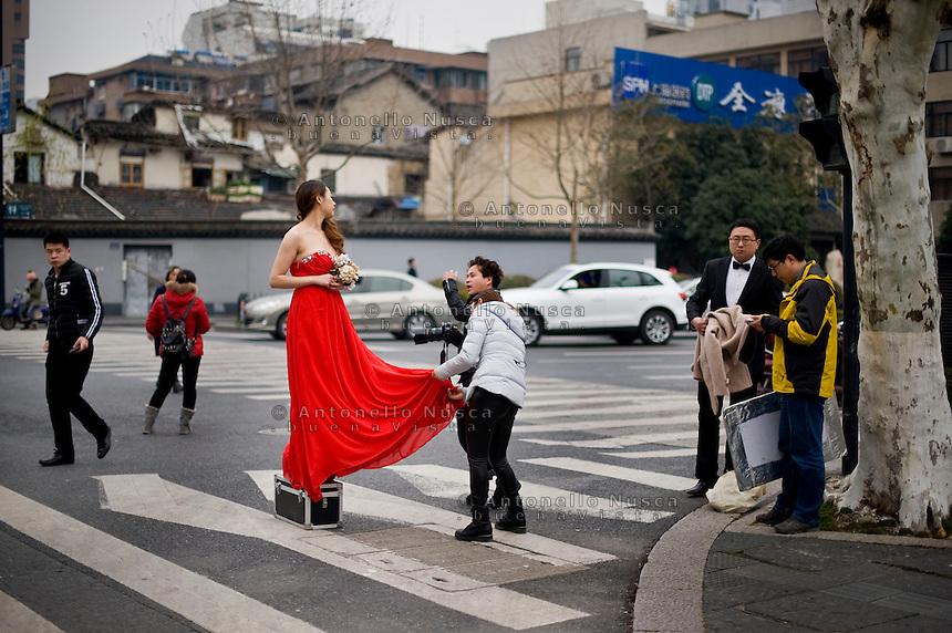 Una coppia di sposi durante il servizio fotografico.<br /> Young wedded during the photo section in the center of Hangzhou